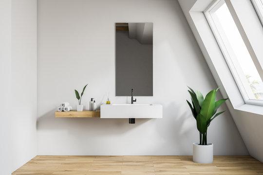 Interior of white attic bathroom with sink