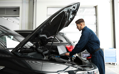 Technician checking car with laptop at automobile repair shop