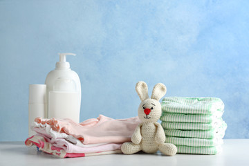 Stack of diapers and baby accessories on table against color background. Space for text Wall mural