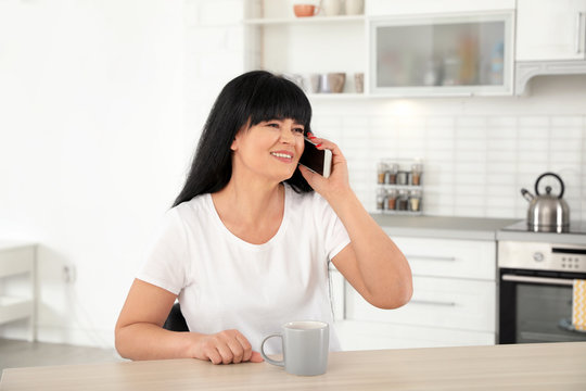 Mature woman with cup of drink and smartphone sitting at table indoors