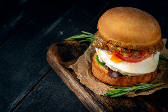 Homemade vegetarian Burger with mozzarella and fried eggplant on a wooden Board on a dark background. Healthy and proper nutrition, rustic style
