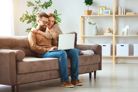 happy couple with laptop computer at home  .