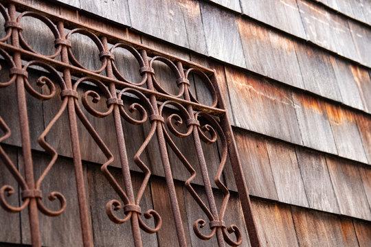 Weathered wood shingle siding and rusty wrought iron metal gate