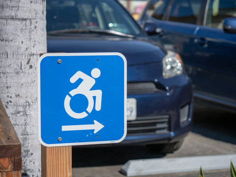 Wheel chair traffic sign pointing to the right in a parking lot