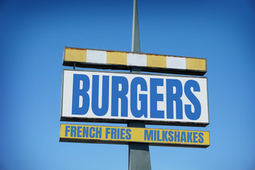 aged and worn retro burgers and fries sign