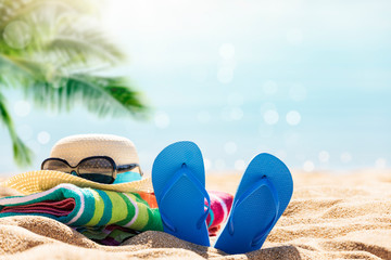 Beach accessories straw hat, flip flops, towel on sunny tropical beach, summer holidays