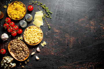 Different types of raw paste in bowls with tomatoes, garlic and mushrooms.
