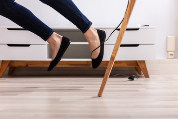 Woman Legs Stumbling With An Electrical Cord
