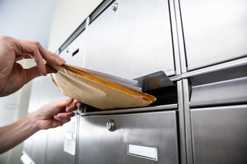 Person's Hand Inserting Envelopes In Mailbox