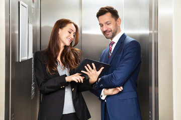Businesspeople Discussing Standing Near Elevator
