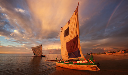 Traditional fishing pirogue at sunset with dramatic sky after a thunderstorm in Anakao, Madagascar Wall mural