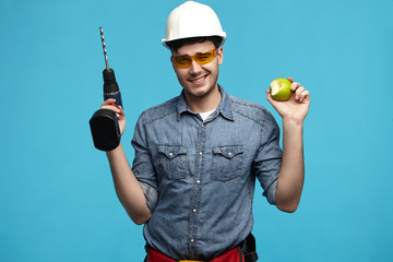 Studio picture of hardworking handsome young handyman wearing hardhat and glasses posing at blue wall with drill in one hand and green apple in other, having lunch break while doing repair works
