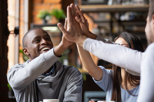 Cheerful different ethnicity friends sitting in cafe giving high five