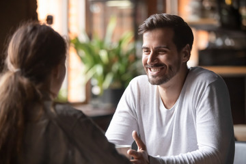 Rear view female sitting at speed dating with smiling man