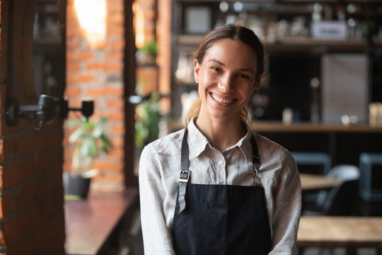 Happy mixed race female in apron smiling looking at camera