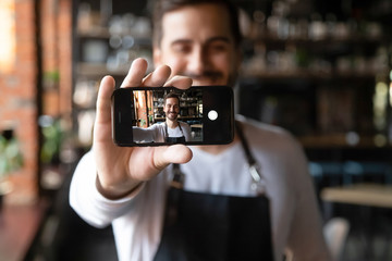 Smiling restaurant owner holding smartphone with camera on make selfie