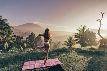 woman with dark hair in sportive suit making yoga on sunrise with volcano Agung view