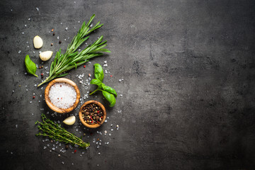 Selection of spices and herbs on dark stone table.