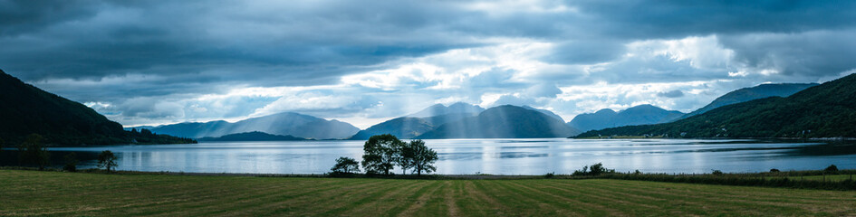 Mystic landscape lake scenery in Scotland: Cloudy sky, meadow, trees and lake with sunbeams, mountain range in the background. Loch Linnhe.
