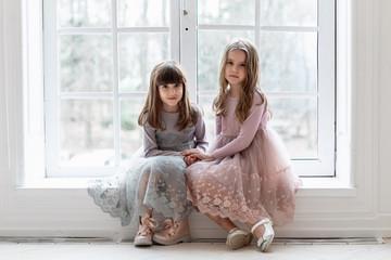 Two little girls with big eyes sit on a windowsill near a large window