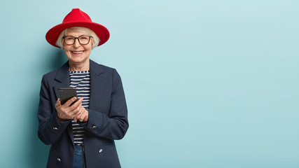 Overjoyed senior lady in stylish apparel and hat chats with friends online, happy to learn using modern gadgets, being advanced user of cell phone, spends leisure time at home, stands indoor alone