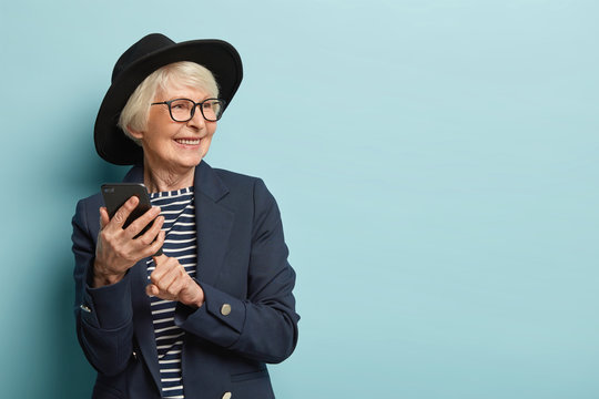 Old attractive woman types text message on cellular, uses new online application, has positive facial expression, looks away, wears stylish headgear and coat, stands over blue studio wall, free space