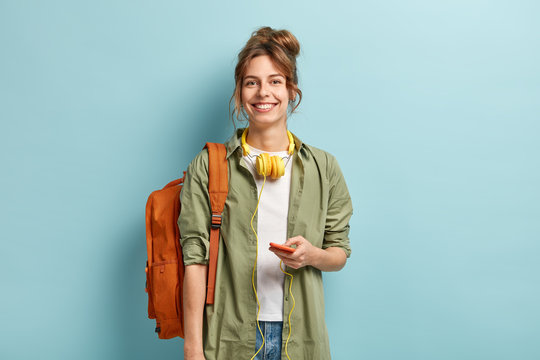 Beautiful smilig female traveller has leisure time, enjoys online communication, connected to headphones, listens music from playlist, wears casual white t shirt and green shirt, carries rucksack