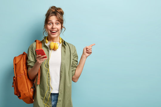 Studio shot of happy teenage girl holds mobile phone, checks email, gets new notification, uses modern headphones, points at copy space for brand name or label, wears loose khaki shirt, carries bag