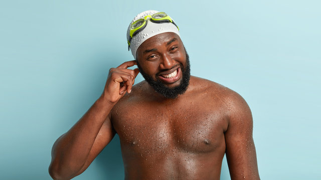 Candid shot of cheerful man has water in ear after diving, being wet, happy after swimming during sunny summer weather, wears swimcap with goggles, has broad smile, poses indoor. Glad swimmer