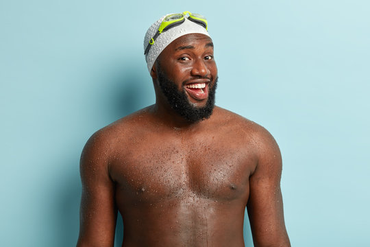 Healthy black man with athletic body shape, smiles at camera, being professional swimmer, comes out of water, feels relaxed and full of energy, wears swimming cap, goggles, isolated on blue wall