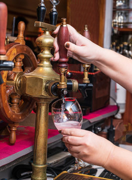 Barman serves the barrel drink. Hand and wine tap.