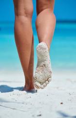 Wall Mural - Woman walking on tropical white sand beach