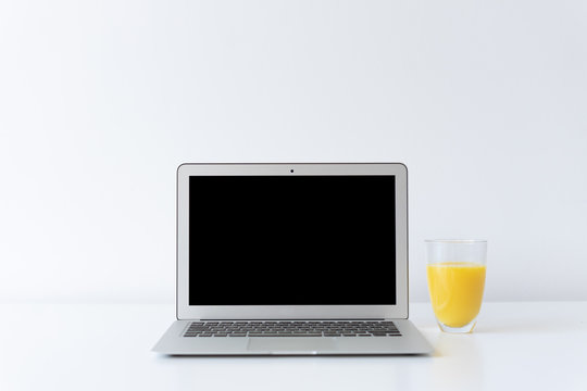 Open laptop and glass of orange juice on the desk with white background