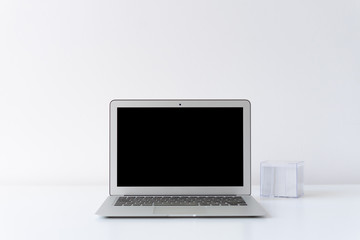 Open laptop and note cube on the desk with white background