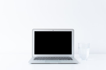 Open laptop and glass of water on the desk with white background