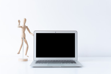 Open laptop and wooden figure model on the desk with white background