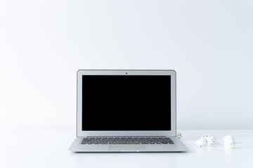 Open laptop and small easter eggs on the desk with white background
