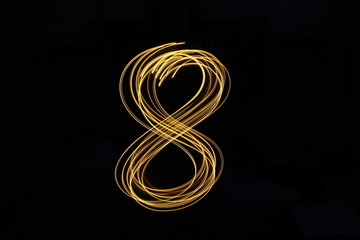 Long exposure, light painting photography.  Single number in a vibrant neon metallic yellow gold colour against a black background
