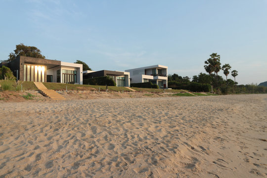Front view of house on the beach and a setting sun, real estate