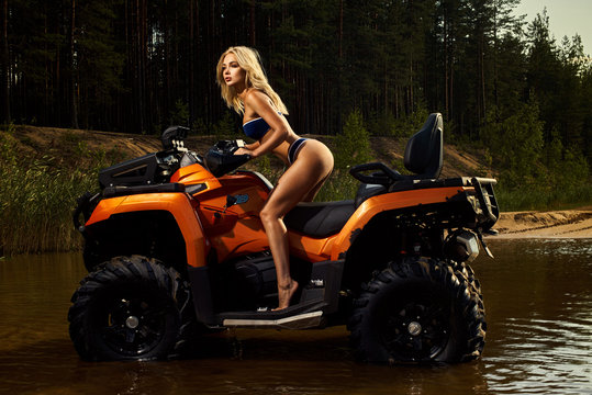 Beautiful blonde girl on a orang ATV rides on the river, standing on the mountain. Around the forest, sand and blue sky.She rides on a green swamp, in the mud and all wet. She's wearing a blue bikini.