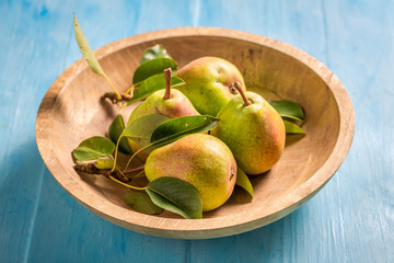 Sweet pears in brown bowl on blue table