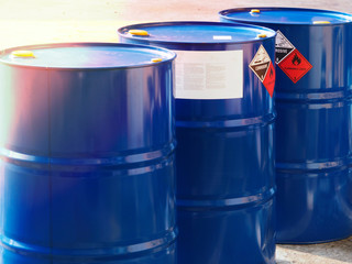 the close-up shot of blue color hazardous dangerous chemical drum barrels ,have warning labels of corrosive & flammable liquid in daylight on daytime.