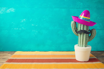 Photo sur Plexiglas Cactus Cinco de Mayo holiday background with Mexican cactus and party sombrero hat on wooden table