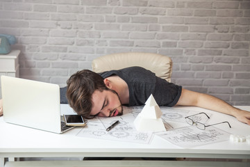 Man designers sleeping because of fatigue from work.