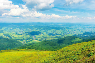 wonderful mountain landscape in summer.  green grassy hills and slopes. path downhill through the meadow. settlement and rural area in the distant valley. sunny weather with fluffy clouds on the sky