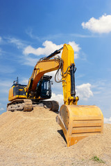 Yellow excavator on a pile of dirt with blue sky with white clouds in the background