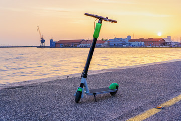 Parked electric Scooter rental without passenger. A green and black ride sharing scooter ready to be used by the next rider on the streets of Thessaloniki, Greece.