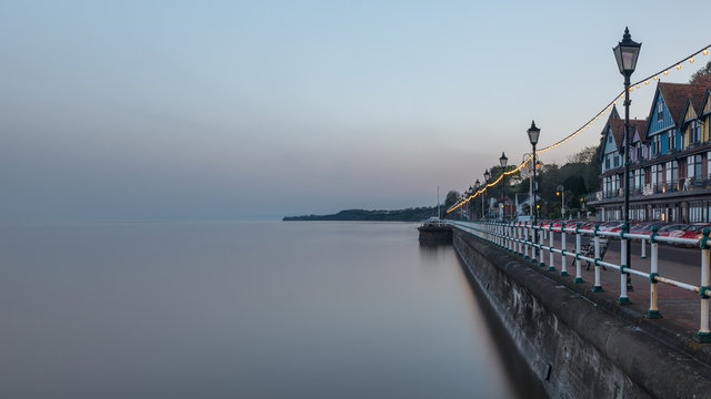 Penarth seafront, near Cardiff on the south Wales coast. It is evening and the tide is in. The sea is smooth due to a long shutter speed.