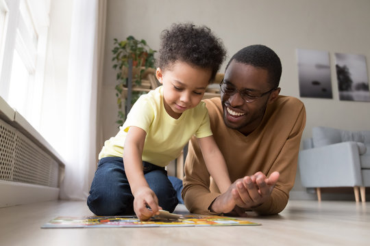 African father and little son collect jigsaw puzzle at home