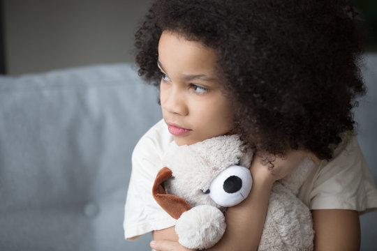 Unfortunate stray biracial kid girl embrace stuffed toy looking aside
